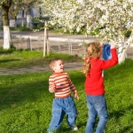 Happy small children in spring recreation ground