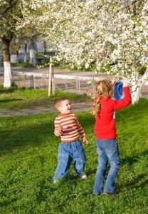 Happy small children in spring recreation ground